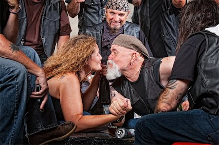Two biker gang lovers kiss while arm wrestling Stock Photo - Budget Royalty-Free & Subscription, Code: 400-06396543