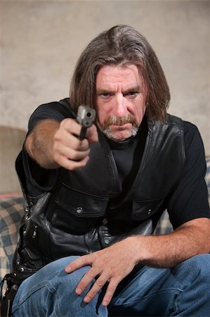Suspicious male in biker gang clothing aiming a pistol Stock Photo - Budget Royalty-Free & Subscription, Code: 400-06396849