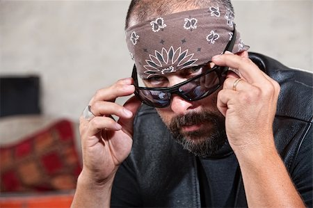 Intimidating male biker in bandana looking over his sunglasses Stock Photo - Budget Royalty-Free & Subscription, Code: 400-06396855
