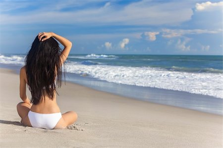 simsearch:400-04002563,k - A sexy young brunette woman or girl wearing a white bikini sitting on a deserted tropical beach with a blue sky Stock Photo - Budget Royalty-Free & Subscription, Code: 400-06421494