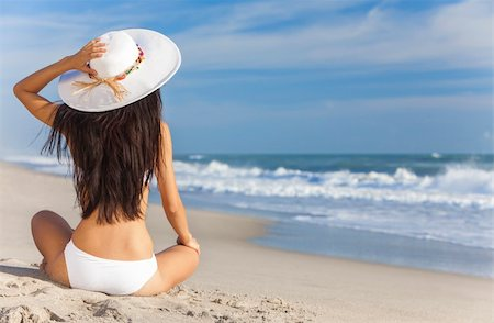 simsearch:400-04002563,k - A sexy young brunette woman or girl wearing a white bikini and sun hat sitting on a deserted tropical beach with a blue sky Stock Photo - Budget Royalty-Free & Subscription, Code: 400-06421490