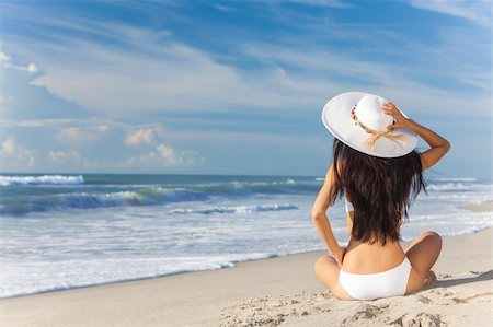 simsearch:400-04002563,k - A sexy young brunette woman or girl wearing a white bikini and sun hat sitting on a deserted tropical beach with a blue sky Stock Photo - Budget Royalty-Free & Subscription, Code: 400-06421491