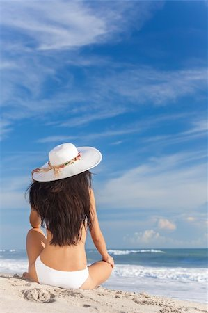 simsearch:400-04002563,k - A sexy young brunette woman or girl wearing a white bikini and sun hat sitting on a deserted tropical beach with a blue sky Stock Photo - Budget Royalty-Free & Subscription, Code: 400-06421492