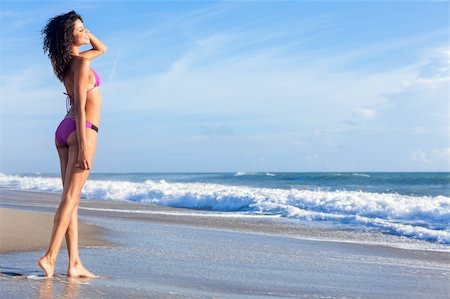 simsearch:400-04002563,k - A sexy young brunette woman or girl wearing a purple bikini on a deserted tropical beach with a blue sky Stock Photo - Budget Royalty-Free & Subscription, Code: 400-06421522