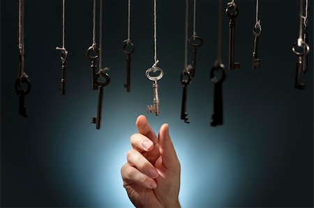 Hand choosing a hanging key amongst other ones. Stock Photo - Budget Royalty-Free & Subscription, Code: 400-06422988