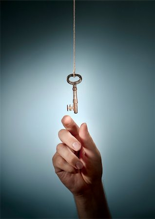 Conceptual image of a hand taking an old key hanging from a string. Stock Photo - Budget Royalty-Free & Subscription, Code: 400-06423013