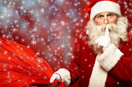 Portrait of Santa Claus with huge red sack keeping forefinger by his mouth and looking at camera Stock Photo - Budget Royalty-Free & Subscription, Code: 400-06458422