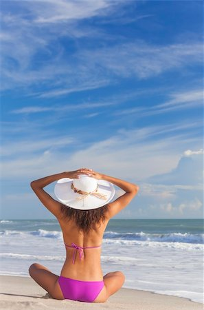 simsearch:400-04002563,k - A sexy young brunette woman or girl wearing a bikini and sun hat sitting on a deserted tropical beach with a blue sky Stock Photo - Budget Royalty-Free & Subscription, Code: 400-06458506