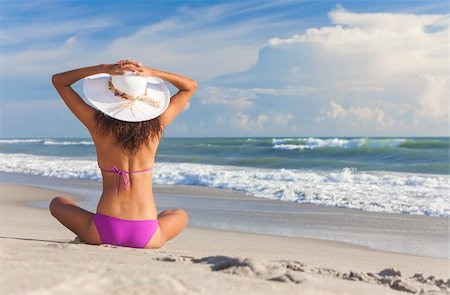 simsearch:400-04002563,k - A sexy young brunette woman or girl wearing a bikini and sun hat sitting on a deserted tropical beach with a blue sky Stock Photo - Budget Royalty-Free & Subscription, Code: 400-06458508