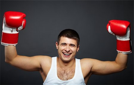 Portrait of happy young man in red boxing gloves looking at camera Stock Photo - Budget Royalty-Free & Subscription, Code: 400-06459715