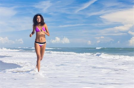 simsearch:400-04002563,k - A sexy young brunette woman or girl wearing a bikini running through the surf on a deserted tropical beach with a blue sky Stock Photo - Budget Royalty-Free & Subscription, Code: 400-06463545