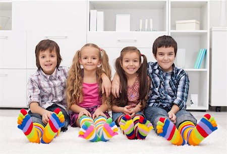 stocking feet - Happy children sitting on the carpet wearing colorful socks Stock Photo - Budget Royalty-Free & Subscription, Code: 400-06483684