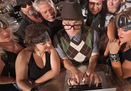 Mature nerd troubleshooting a computer with biker gang Stock Photo - Budget Royalty-Free & Subscription, Code: 400-06525844