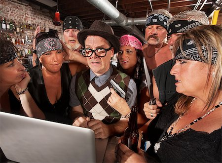 Worried nerd on laptop with suspicious motorcycle gang Stock Photo - Budget Royalty-Free & Subscription, Code: 400-06525845