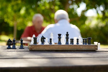 diego_cervo (artist) - Active retirement, old friends and leisure, two senior men having fun and playing chess game at park. Focus on chessboard in foreground Stock Photo - Budget Royalty-Free & Subscription, Code: 400-06530999