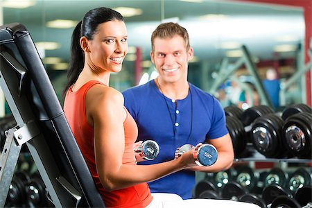 Woman with her personal fitness trainer in the gym exercising with dumbbells Stock Photo - Budget Royalty-Free & Subscription, Code: 400-06557124