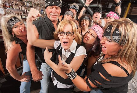 Amazed motorcycle gang looking at nerd showing off muscles Stock Photo - Budget Royalty-Free & Subscription, Code: 400-06557774