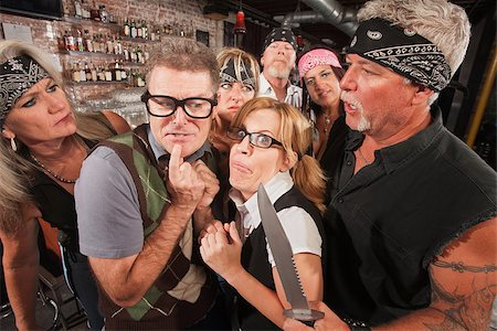 Scared geek couple in bar surrounded by tough gang Stock Photo - Budget Royalty-Free & Subscription, Code: 400-06557776