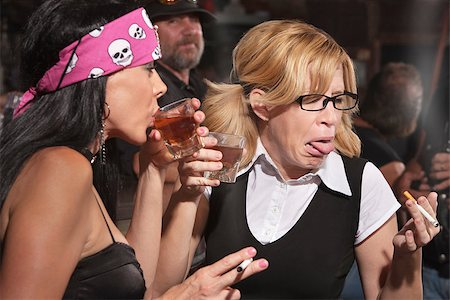 Female nerd sticking out tongue after tasting whiskey in bar Stock Photo - Budget Royalty-Free & Subscription, Code: 400-06558616