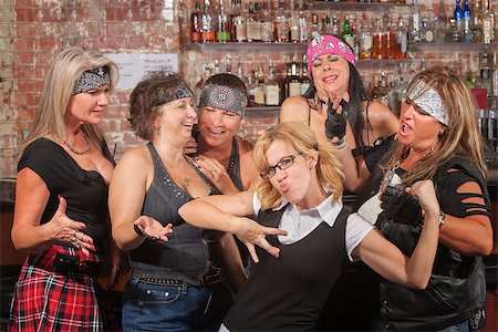 Nerd flexes muscles for tough female gang in bar Stock Photo - Budget Royalty-Free & Subscription, Code: 400-06561345