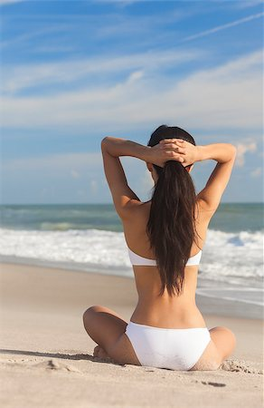 simsearch:400-04002563,k - A sexy young brunette woman or girl wearing a white bikini sitting cross legged on a deserted tropical beach with a blue sky Stock Photo - Budget Royalty-Free & Subscription, Code: 400-06562526