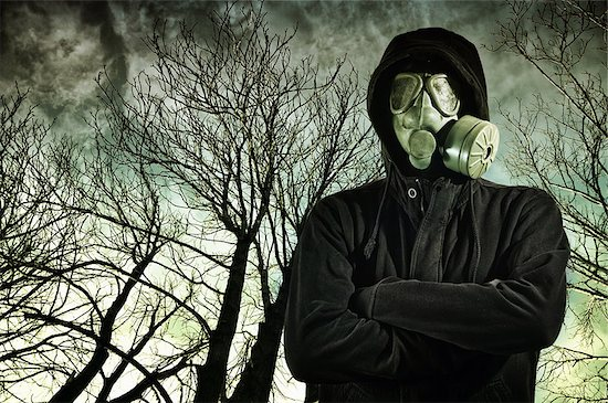 Man in dark clothes wearing a classic gas mask respirator, tree branches in the background. Stock Photo - Royalty-Free, Artist: stevanovicigor, Image code: 400-06643747