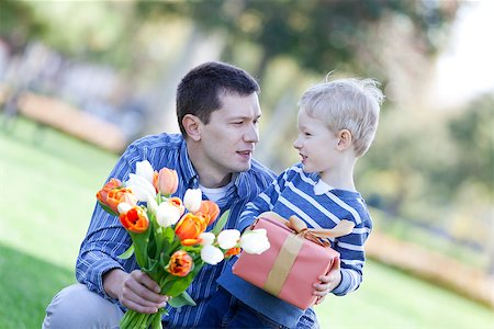 handsome young man and child offering a gift and flowers Stock Photo - Budget Royalty-Free & Subscription, Code: 400-06701371