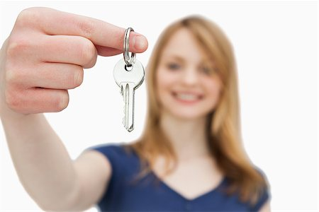 finger holding a key - Focus shot on a woman holding a key against a white background Stock Photo - Budget Royalty-Free & Subscription, Code: 400-06735237