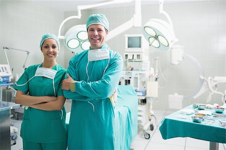 Surgeons standing up while smiling in an operating theatre Stock Photo - Budget Royalty-Free & Subscription, Code: 400-06735506