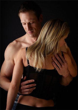 Young and fit caucasian adult couple in an embrace. Semi-nude and topless against a dark background with the woman wearing a sexy red and black lace corset. Stock Photo - Budget Royalty-Free & Subscription, Code: 400-06736219