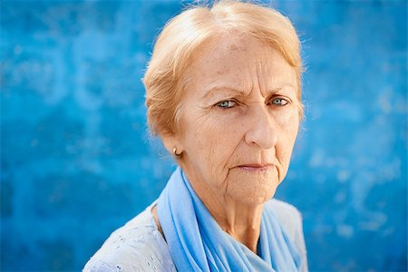 diego_cervo (artist) - Senior people portrait, happy sad blonde woman in blu clothes looking at camera against blue wall Stock Photo - Budget Royalty-Free & Subscription, Code: 400-06737356