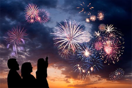 The happy family looks beautiful colorful holiday fireworks in the evening sky with majestic clouds,  long exposure Stock Photo - Budget Royalty-Free & Subscription, Code: 400-06744743