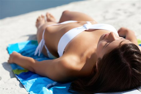 pressmaster (artist) - Image of female in white bikini sunbathing on sandy beach during vacation Stock Photo - Budget Royalty-Free & Subscription, Code: 400-06742543