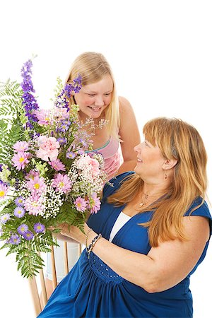 Beautiful blond teenage girl giving flowers to he mother.   Mothers Day concept.  Isolated on white. Stock Photo - Budget Royalty-Free & Subscription, Code: 400-06759359
