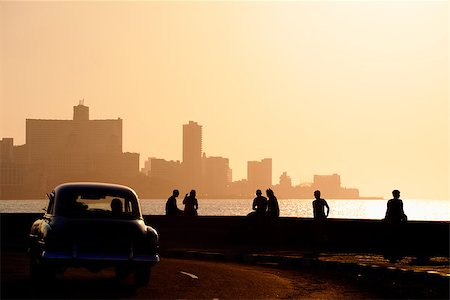 diego_cervo (artist) - Skyline in La Habana, Cuba, at sunset, with vintage cars on the street and people sitting on the Malecon. Copy space Stock Photo - Budget Royalty-Free & Subscription, Code: 400-06770212