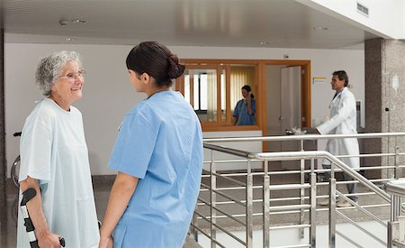 Nurse talking with a patient who is walking with crutches in a hospital Stock Photo - Budget Royalty-Free & Subscription, Code: 400-06799498