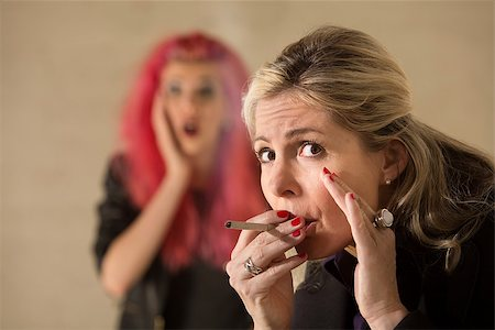 Surprised teen behind mature woman smoking a cigarette Stock Photo - Budget Royalty-Free & Subscription, Code: 400-06790525