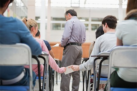 passing of papers in the classroom - Students passing a note behind teacher's back in classroom Stock Photo - Budget Royalty-Free & Subscription, Code: 400-06803100
