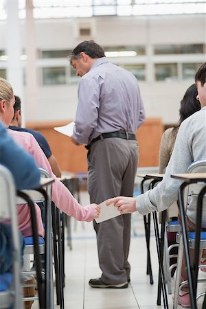 passing of papers in the classroom - Students passing notes as teacher is talking to student in classroom Stock Photo - Budget Royalty-Free & Subscription, Code: 400-06803101