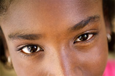 Closeup of eyes of pretty happy young african girl looking at camera and smiling Stock Photo - Budget Royalty-Free & Subscription, Code: 400-06854114