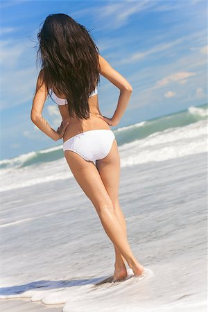 simsearch:400-04002563,k - Rear view of a sexy young brunette woman or girl wearing a white bikini standing in the surf on a deserted tropical beach with a blue sky Stock Photo - Budget Royalty-Free & Subscription, Code: 400-06850924