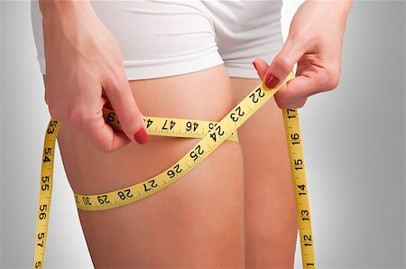 Woman measuring her thigh with a yellow measuring tape Stock Photo - Budget Royalty-Free & Subscription, Code: 400-06853112