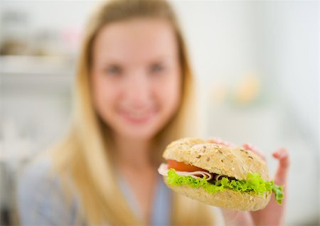 Closeup on burger in hand of teenager girl Stock Photo - Budget Royalty-Free & Subscription, Code: 400-06853554