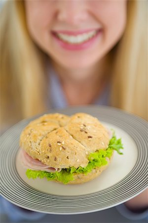 Closeup on plate with sandwich in hand of smiling teenager girl Stock Photo - Budget Royalty-Free & Subscription, Code: 400-06853553