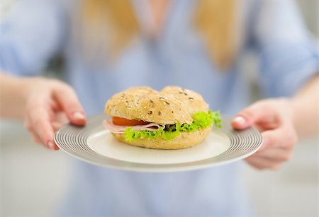 Closeup on plate with sandwich in hand of young woman Stock Photo - Budget Royalty-Free & Subscription, Code: 400-06853593