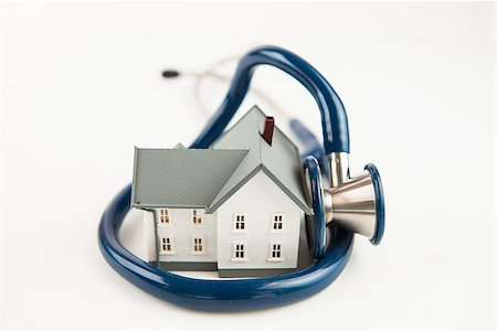 Blue stethoscope wrapped aroud tiny house model on white background Stock Photo - Budget Royalty-Free & Subscription, Code: 400-06864406