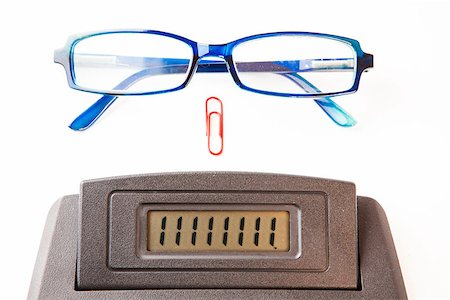 Sector of calculator display with blue glasses and red paper clip Stock Photo - Budget Royalty-Free & Subscription, Code: 400-06864439