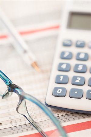 Shot of calculator and glasses lying on statistic table Stock Photo - Budget Royalty-Free & Subscription, Code: 400-06864431
