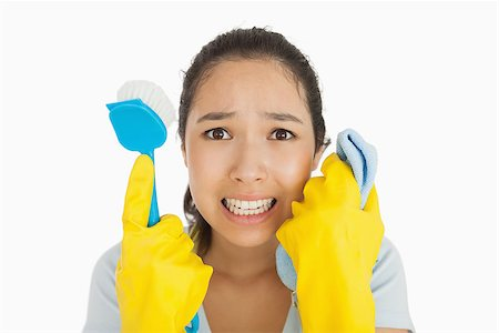 rubber apron woman - Distressed woman holding cloth and scrubbing brush in apron and rubber gloves Stock Photo - Budget Royalty-Free & Subscription, Code: 400-06866414