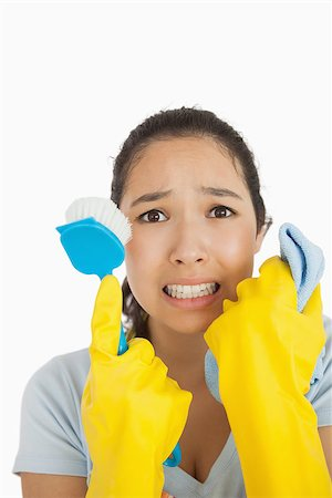 rubber apron woman - Stressed woman holding scrubbing brush and rag wearing rubber gloves Stock Photo - Budget Royalty-Free & Subscription, Code: 400-06866416